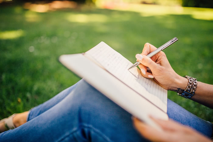 Woman sitting in grass writting in a notebook