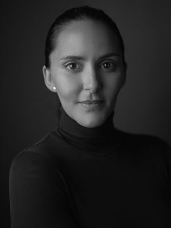Dr. Leah Houston with arms crossed, hair back in black and white photo