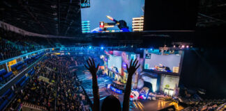 excited fan standing up cheering in an esports stadium