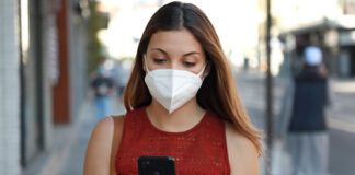 girl with mask looking at cellphone and walking