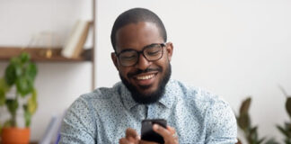 smiling african-american texting on his mobile phone