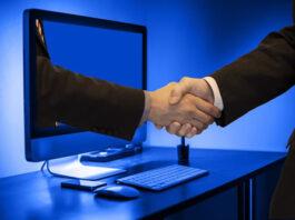 Two men handshaking through a PC monitor