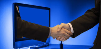 Two men handshaking through a PC monitor