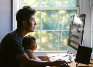 father and child sitting at home office desk and computer