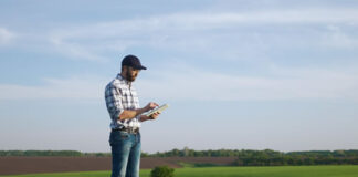farmer using technology tablet in a large field