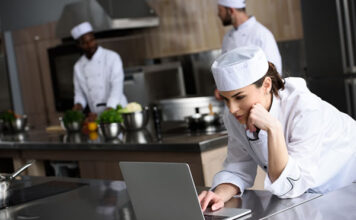 woman chef on laptop in restaurant kitchen