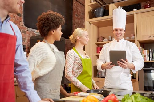 4 chefs in kitchen monitoring their culinary with technology