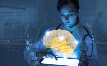 physician holding tablet with a hologram of a digital brain floating