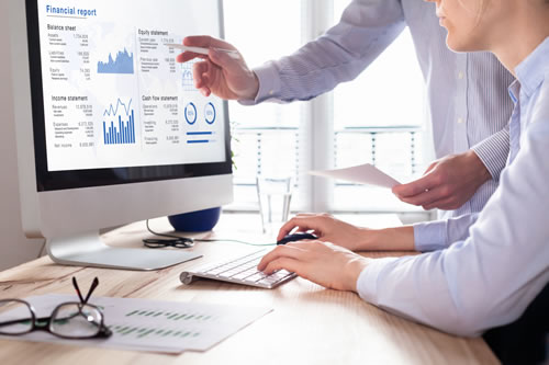 woman and man reviewing a financial dashboard on a computer