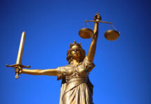 bronze statue of Lady Justice with blue sky background