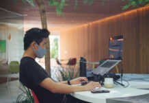 man with mask working remote on his laptop