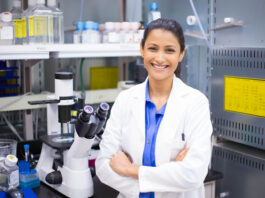 Smiling woman scientist in lab with arms crossed looking at camera