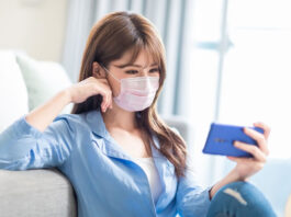 woman wearing mask sitting on couch reading cell phone