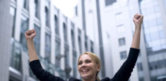 woman in business suit celebrating with hands in air