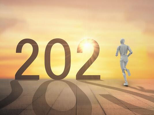 year 2021 with robot running towards sunset horizon