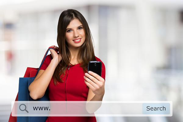smiling girl holding up mobile phone and holding shopping bags