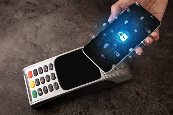 woman holding cellphone next to POS credit card machine