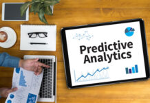 top-down view of man at desk with tablet that says predictive analytics