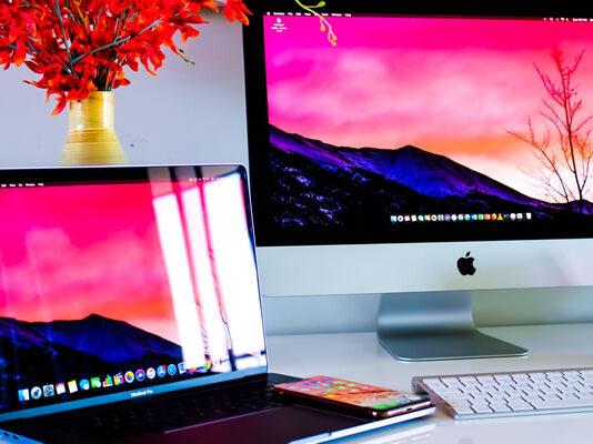 two apple macs sitting on a desk