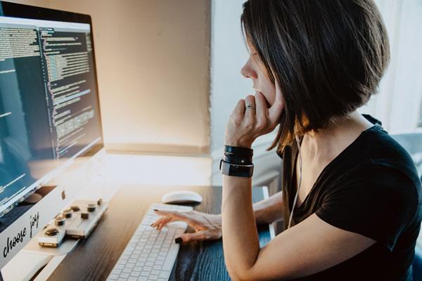 girl developer writing code at her desk