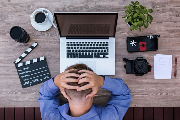 man slouched over frustrated with macbook