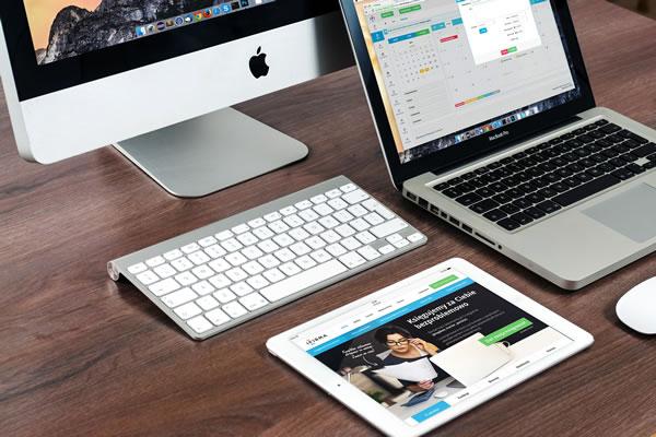 macbook, ipad, and mac neatly arranged on a desk