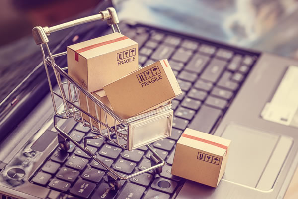 miniature shopping cart and boxes sitting on laptop keyboard