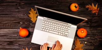 top view of girl typing on laptop with autumn leaves and pumpkins around