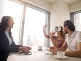 3 people sitting at a table while one person is viewing a presentation with vr goggles