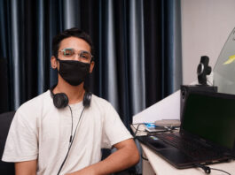 developer at work desk with mask on looking at camera