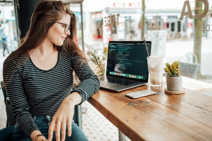 girl developer writing code on her laptop at a coffee shop