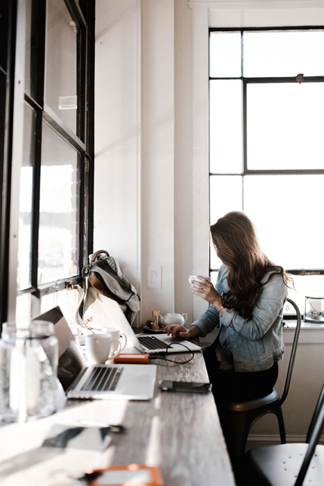 girl sipping coffee and working in coffee shop