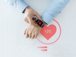 top view of man checking his smart watch on his wrist with heart icon on the face