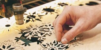 man cutting out snowflakes on poster board with laser cutter