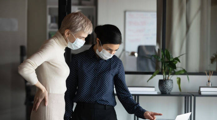 two executive women working in office with masks on