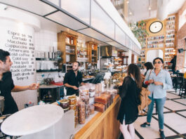 customers awaiting their coffee at a local coffee shop with smiling baristas