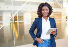 black women business leader holding ipad and smiling into camera