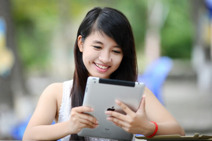 smiling girl holding and reading her ipad outside at a table
