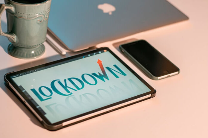 laptop, tablet, and cell phone on a desk with coffee cup displaying the words lockdown
