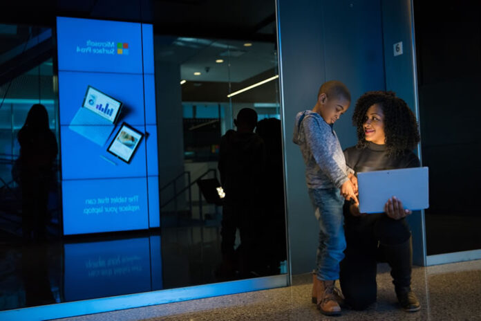 young women tech professional squatting down to show her son on a laptop