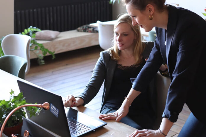 two women discussing business success at a desk with a laptop