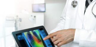 physician holding a tablet displaying a 2d radiology image