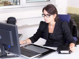 woman executive at her desk handling tasks on her computer