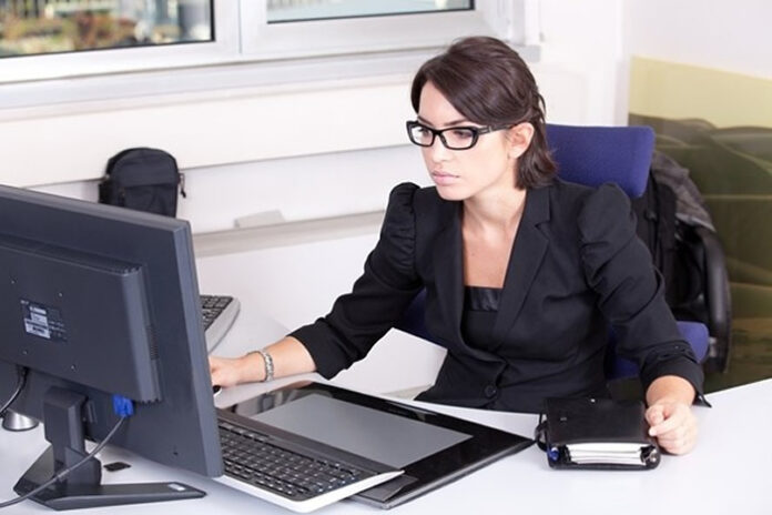 woman executive at her desk handling tasks on her computer