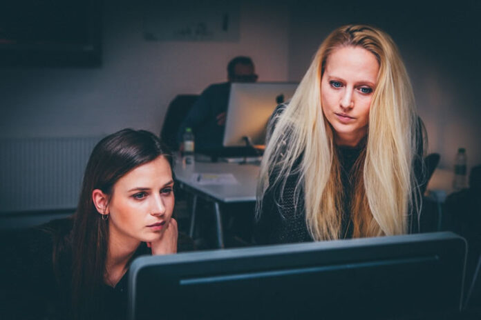women working in staff augmentation together on a pc