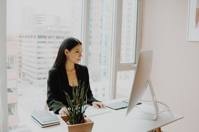 professional woman at desk building a strong personal brand on LinkedIn