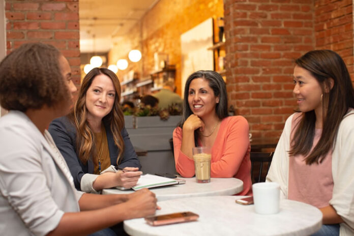four business women in a discussion at a table on women's day