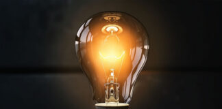 picture of a yellowish light bulb lit up in a dark room