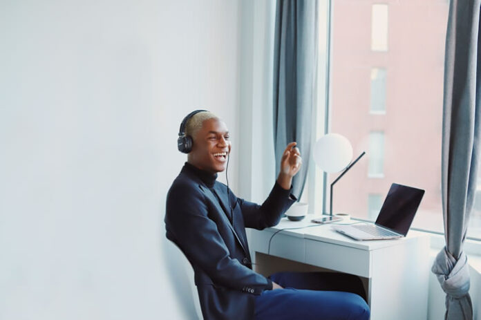 young man smiling as he has a remote meeting on Zoom