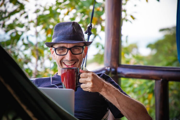 man smiling as he sips his coffee working remotely from his front porch